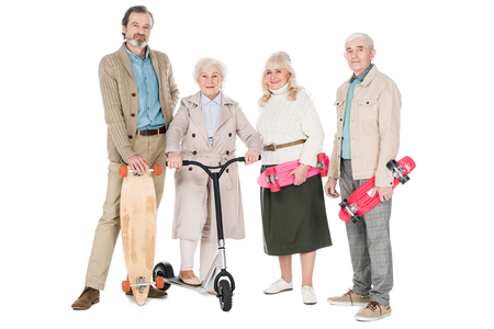 cheerful pensioners standing with skateboards near women on scooter isolated on white Фото со стока