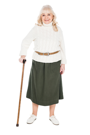 happy retired woman standing with walking cane isolated on white
