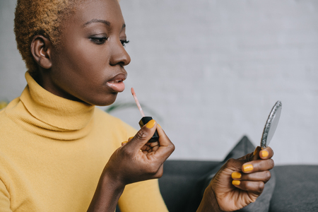 pensive african american woman applying lip gloss and looking in mirror Stock Photo