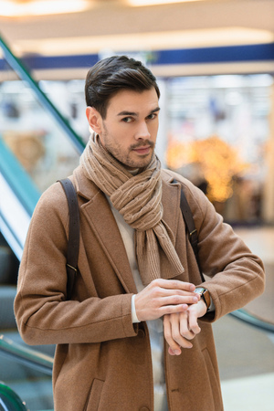 handsome man in warm clothing standing near escalator and touching watch in shopping mall
