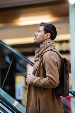 handsome man going up on escalator in shopping mall Stock fotó