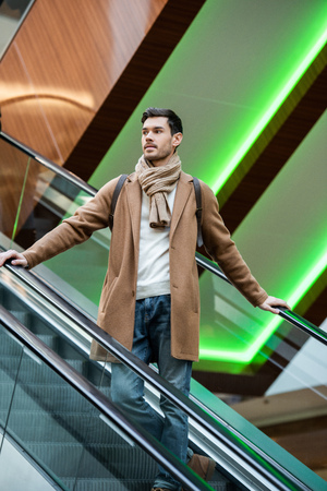 handsome man in warm clothing going down on escalator in shopping mall Banco de Imagens
