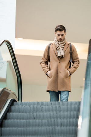 handsome man in warm clothing approaching escalator in shopping mall
