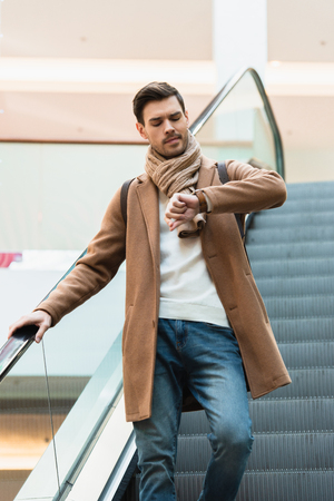 handsome man in going down on escalator and looking at watch in shopping mall Banco de Imagens - 117782783