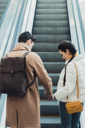 beautiful couple holding hands and going up on escalator Banco de Imagens