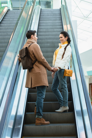 smiling couple in warm clothing holding hands, looking at each other and going up on escalator