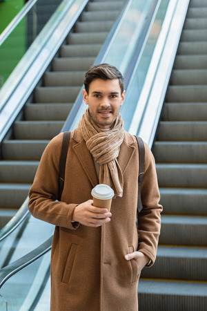 handsome man holding disposable cup and smiling on escalator