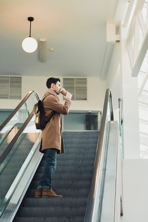 handsome man going up on escalator and drinking from disposable cup