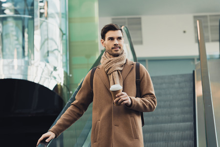 handsome man in warm clothing holding paper cup and going down on escalator Banco de Imagens - 117782797
