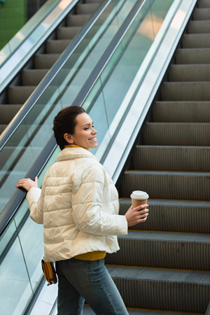 beautiful girl smiling, going up on escalator and holding paper cup Banco de Imagens