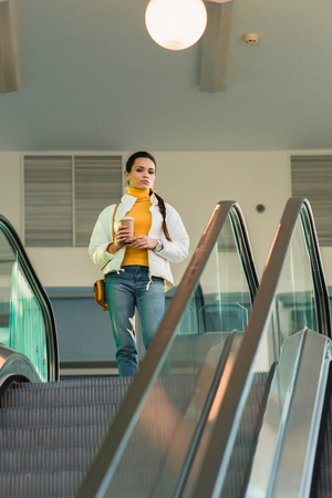 attractive girl with disposable cup standing at top of escalator