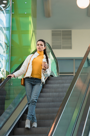 attractive girl holding paper cup, looking at camera and going down on escalator