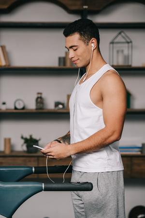 handsome bi-racial sportsman listening music in earphones while using smartphone