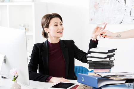 secretary giving cocktail to beautiful smiling businesswoman in office