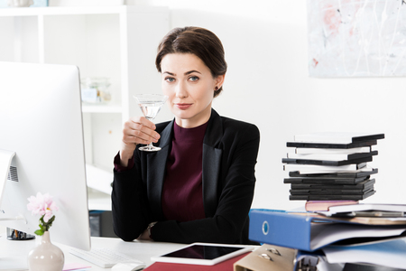 beautiful businesswoman holding cocktail in office Stockfoto