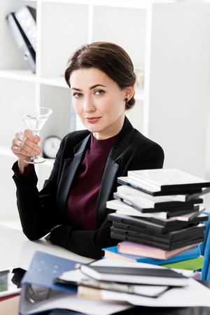attractive businesswoman holding cocktail in office and looking at camera Stockfoto