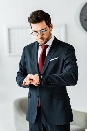 Gut aussehender Geschäftsmann in formeller Kleidung, der im Büro auf die Uhr schaut Standard-Bild