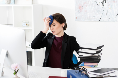 businesswoman having headache and touching head with ice pack in office Stock Photo