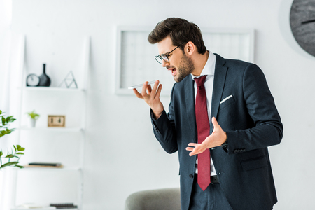 angry businessman in formal wear yelling at smartphone during conversation in office