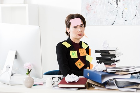 upset attractive businesswoman sitting with stickers on face and clothes in office, looking at camera Stock Photo
