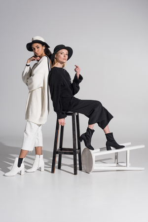 attractive multiethnic women in black and white clothes posing with chairs on white Imagens