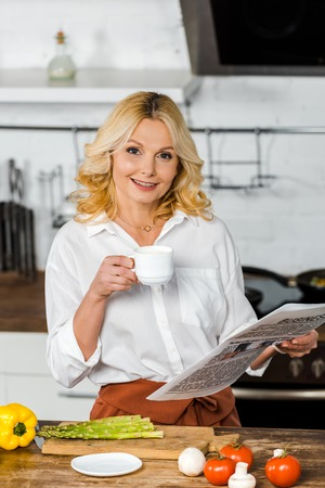 attractive middle aged woman holding cup of tea and reading newspaper in kitchen, looking at camera
