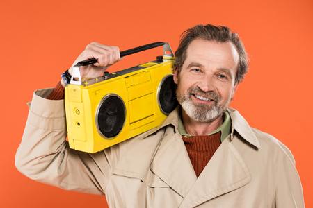 cheerful senior man holding yellow boombox isolated on orange Stock Photo