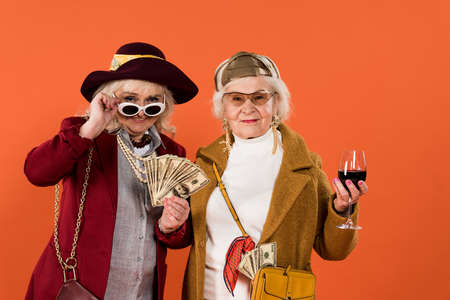 senior woman touching sunglasses while holding money near friend with glass of wine in hand isolated on orange Stock Photo