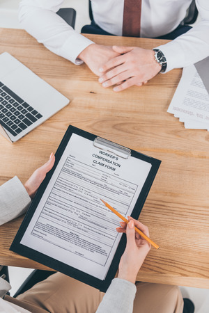 cropped view of businessman sitting at wooden desk while woman filling in compensation claim form Фото со стока