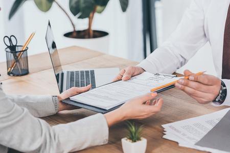 Ausgeschnittene Ansicht eines Geschäftsmannes, der einer Frau am Arbeitsplatz ein Entschädigungsantragsformular gibt Standard-Bild