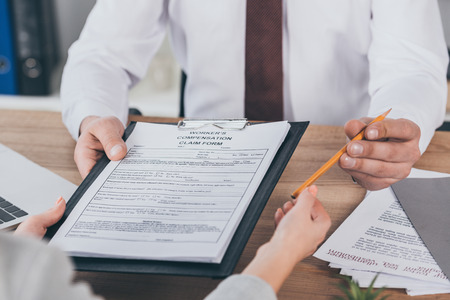 cropped view of businessman giving clipboard with compensation claim form and pencil to woman at workplace
