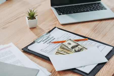 clipboard with compensation claim form and open envelope with money lying over on office desk, compensation concept Zdjęcie Seryjne - 117783783