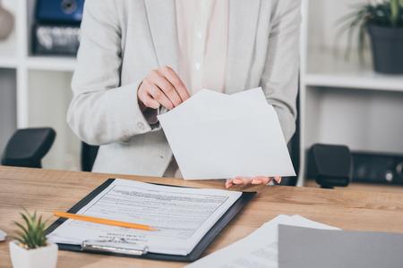 Ausgeschnittene Ansicht der Geschäftsfrau, die Geld in einen offenen Umschlag steckt, während sie am Schreibtisch sitzt, Vergütungskonzept
