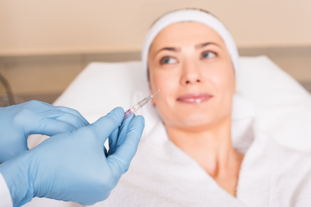 selective focus of syringe holding by cosmetologist over woman face at beauty salon