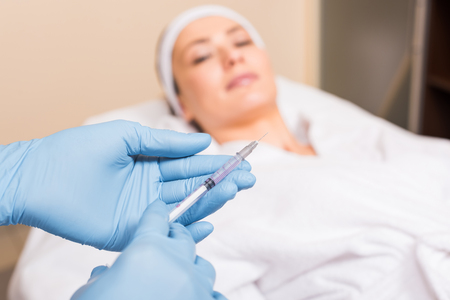 selective focus of syringe holding by beautician in front of woman face at beauty salon