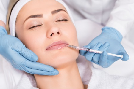 beautician doing injection on lip to woman at beauty salon