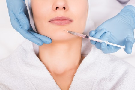 cropped view of beautician injecting face woman at beauty salon