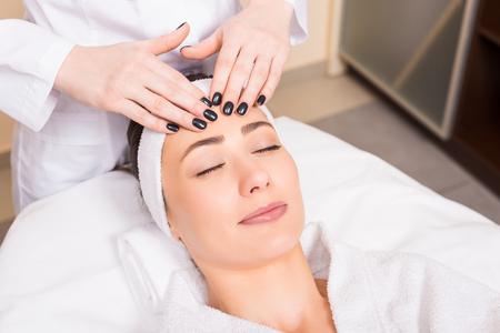 schoonheidsspecialiste die handmatige gezichtsmassage maakt voor vrouw die in schoonheidssalon ligt Stockfoto