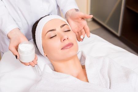 Kosmetikerin, die eine kosmetische Cremeflasche hält und sie im Schönheitssalon auf das Gesicht der Frau legt