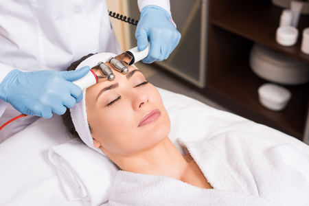 cosmetologist doing face massage by equipment to woman at beauty salon