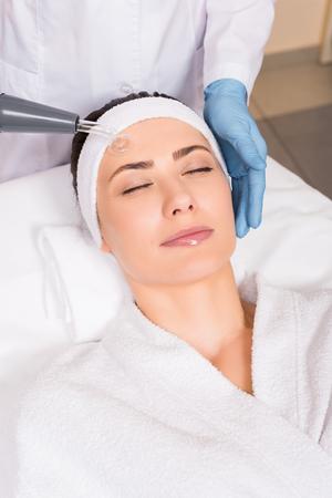 beautician doing darsonvalization to woman on face at beauty salon Banco de Imagens