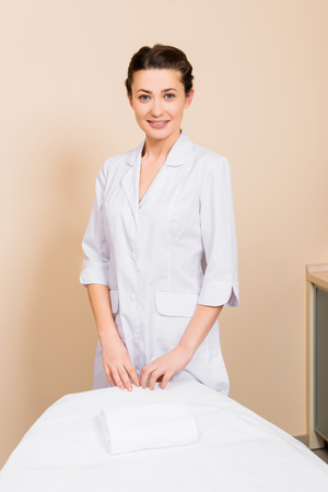 beautician standing behind massage table and smiling at beauty salon Stock Photo