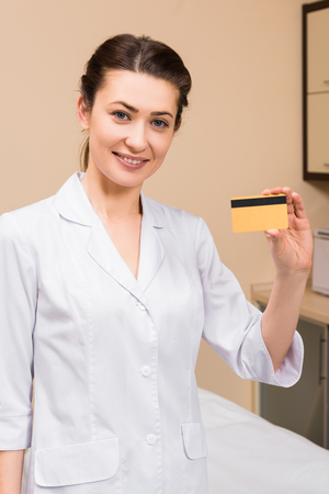 beautician holding credit card and smiling at beauty salon