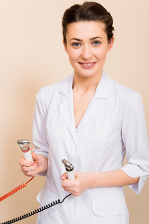 beautician holding massager at beige background