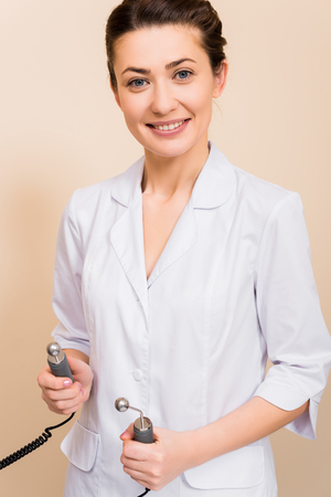 beautician holding lifting massager at beige background