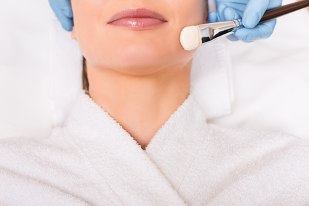 cropped view of beautician applying cosmetic mask on woman face with cosmetic brush at beauty salon Banco de Imagens