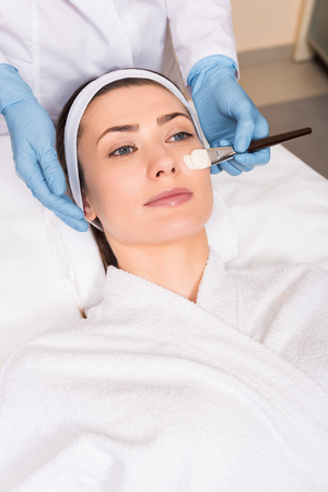beautician applying cosmetic mask on woman face and holding cosmetic brush at beauty salon