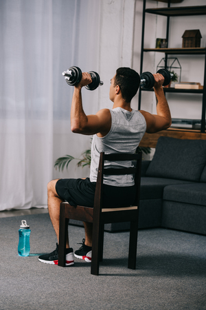 muscular mixed race man holding heavy dumbbells while sitting on chair in apartment