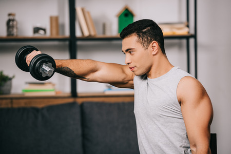 strong mixed race sportsman workout with heavy dumbbell Stock Photo
