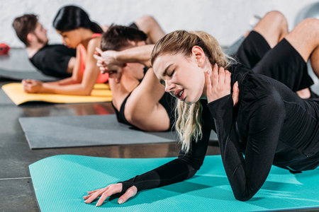 young woman touching injured neck while exercising on yoga mat in gym